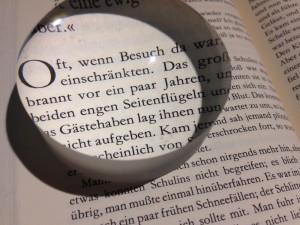 Olvasókö egy könyvnek a szövegét nagyítja